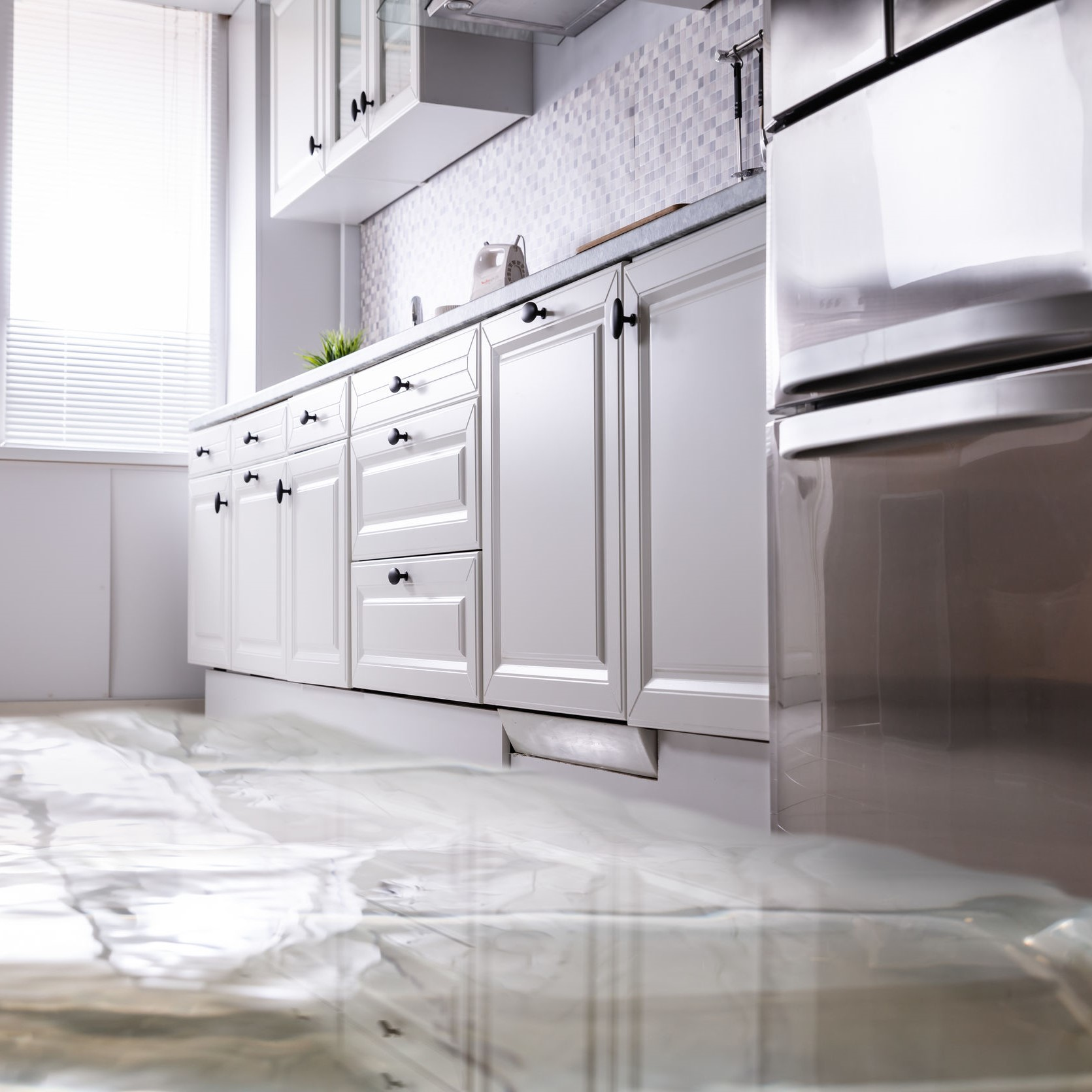 A kitchen that has been flooded due to a leaky or broken pipe.